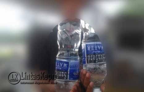 Seorang pemilik warung menunjukkan serbuk-serbuk halus diminuman mineral merek sanford kemasan 1500 Mililiter, (27/09).