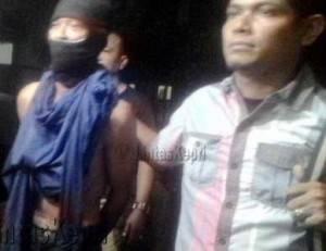 M (Kiri) Ketika Digiring Polisi Ke Ruangan Satreskrim Polresta Tanjungpinang.