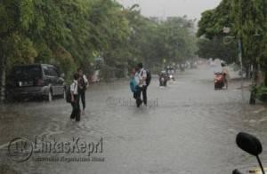 Pelajar berlari ditengah banjir di Jalan Pemuda