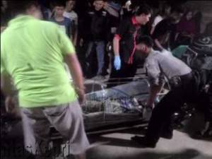 Terlihat petugas kepolisian setempat dibantu warga menggotong mayat menggunakan tanduk untuk dimasukkan kedalam mobil jenazah
