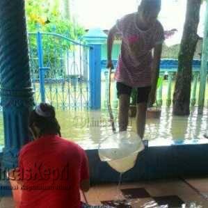 Terlihat warga mengeluarkan air yang masuk kedalam rumah mereka