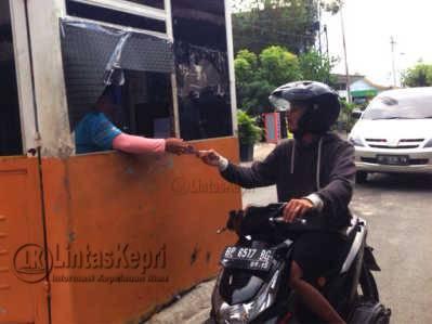 Seorang Pengendara sepeda motor saat membayar di loket parkir pelabuhan SBP, Rabu (25/5).