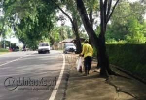 Petugas Kebersihan M saat melakukan tugas rutin menyapu jalan di salah satu Jalan Kota Tanjungpinang