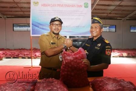 Kepala Kantor Wilayah (KaKanWil) Direktorat Jenderal Bea Dan Cukai (DJBC) Khusus Provinsi Kepulauan Riau (Kepri) Parjiya (kanan) saat menghibahkan bawang merah ke Pemko Tanjungpinang yang diwakili oleh Walikota Tanjungpinang Lis Darmansyah (kiri).
