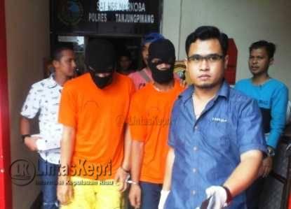 Kasat Narkoba Polres Tanjungpinang AKP Ricky Firmansyah (Kemeja Biru) saat menggiring tersangka narkoba sebelum press rilis di Mapolres Tanjungpinang, Jumat (18/11).