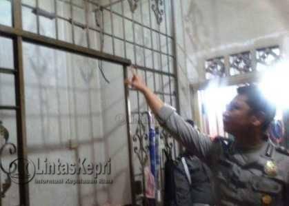 Anggota Polisi saat menunjuk seutas tali nilon yang diduga digunakan korban untuk gantung diri.